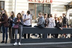 Young people on the street in a crowd. Someone is looking at the phone, waiting for a friend during an unauthorized walk in Moscow