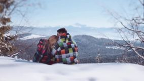 Young people in stylish winter wear. Handsome young boy kissing his lovely girlfriend in forehead while sitting on the. Top of the snowy mountain. Love warmth stock footage