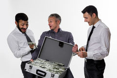 Young people with a suitcase full of money. Royalty Free Stock Image