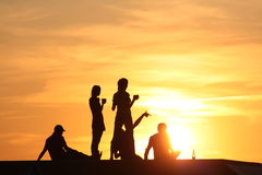 Young people at sunset Stock Images