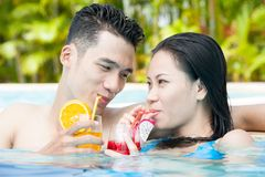 Young people in swimming pool. Couple of young people in swimming pool drinking juice Stock Image