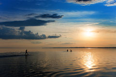 Young people swimming in the river. At sunset Royalty Free Stock Photos