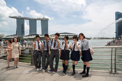 Young people take pictures near Merlion in Singapore Stock Images