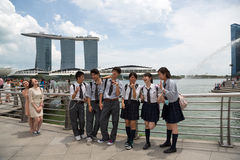 Young people take pictures near Merlion in Singapore Royalty Free Stock Images
