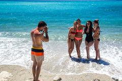 Young people taking photos on beach Royalty Free Stock Images