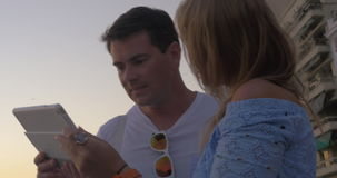 Young people taking sea shots on touch pad. Steadicam shot of young couple using tablet computer to take shots of sea and sunset. Smiling man and woman watching stock footage