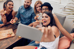 Young people taking a selfie while eating pizza. Group of multiracial young people taking a selfie while eating pizza. Young women eating pizza her friends Stock Photos