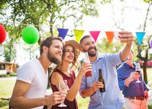 Young people taking selfie at a party outside in the backyard. stock photos