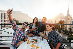 Young people taking selfie on rooftop party. Group of friends having a party on the rooftop making a selfie. Happy young people taking self portrait during party Royalty Free Stock Photo