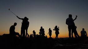Young people taking selfies in the sunset royalty free stock image