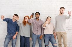 Young people taking selfies on their smartphones stock photography