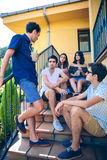 Young people talking outdoors sitting on home stairs steps Royalty Free Stock Images