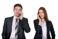 Young people talking on the phones. Portrait of men and women talking on the phones with eyes squinting towards each other Royalty Free Stock Photos