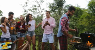 Young People Talking Using Cell Smart Phones While Latin Man Cooking Barbecue Friends Group Cheerful Dancing Gathering. On Summer Terrace Slow Motion 60 stock footage