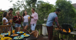 Young People Talking Using Cell Smart Phones While Latin Man Cooking Barbecue Friends Group Gathering On Summer Terrace. Communication Slow Motion 60 stock footage
