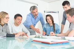 Young people teacher discuss communicate university classroom. Students royalty free stock photos