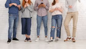 Young people texting on their smartphones, leaning on wall royalty free stock images