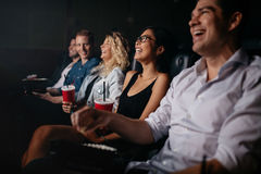Young people in theater watching movie and smiling. Young people sitting in multiplex movie theater watching movie and smiling Royalty Free Stock Images