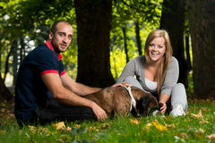 Young People With Their Dog In The Park Royalty Free Stock Image