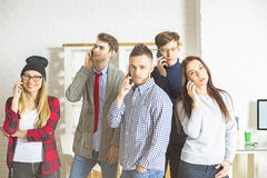Young people on their phones. Group of beautiful young people in office talking on their phones all at once. Communication concept Royalty Free Stock Photo