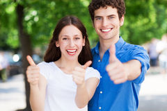 Young people with thumbs up. Smiling Stock Photography
