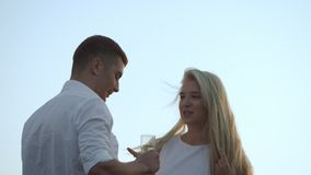 Happy lovers celebrating anniversary. Romantic dating at sunset. Young people toasting champagne at sunset. Smiling lovely couple holding glasses with champagne stock video footage
