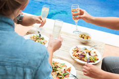 Young people toasting at party by swimming pool Stock Photo
