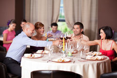 Young people toasting restaurant table. Happy young couples toasting restaurant table Royalty Free Stock Photos