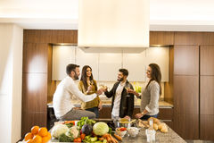 Young people toasting with white wine in the kitchen. People toasting with white wine in the kitchen Royalty Free Stock Photo