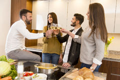 Young people toasting with white wine. In the kitchen Royalty Free Stock Image