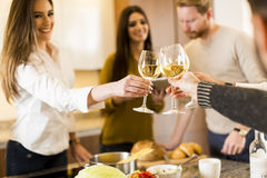 Young people toasting white wine in modern kitchen Stock Image
