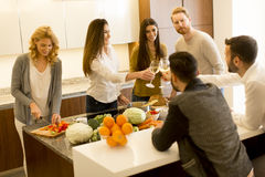Young people toasting white wine in modern kitchen Royalty Free Stock Images
