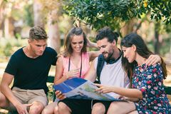 Four smiling traveling young people with map. Young people tourists searching for direction using paper map Royalty Free Stock Image