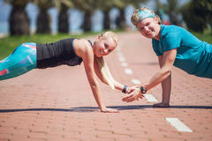 Young people training push up exercise together. By CreativePhotoTeam.com Stock Photo