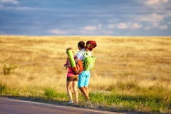 Young people traveling hitchhiking. summer field. Two young people traveling hitchhiking summer field Stock Photo