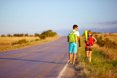 Young people traveling hitchhiking. summer field. Two young people traveling hitchhiking summer field Royalty Free Stock Photo