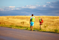 Young people traveling hitchhiking. summer field Royalty Free Stock Photo