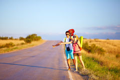 Young people traveling hitchhiking. summer road. Two young people traveling hitchhiking summer field Stock Image