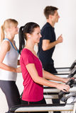Young people on treadmill running exercise Stock Photography