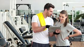 Young people using digital tablet at gym. Young sporty attractive people looking at computer table and talking at fitness club. Sport and technology stock video