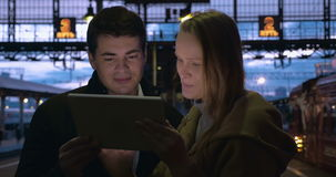 Young people using pad at station in the evening. Young man and woman using tablet computer at the railway station in the late evening while waiting for the stock footage