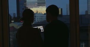 Young people using pad by the window at night. Man and woman using tablet computer to look through the photos. They standing by the window with city view at home stock video