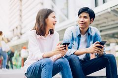 Young people are using smartphone and smiling while sitting on free time. royalty free stock photos