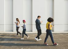 Young people using smartphones outdoors. Young adults using smartphones as they are walking outdoors royalty free stock images