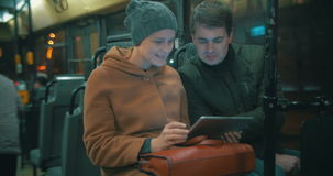 Young people using tablet computer in the bus stock video