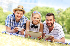 Young people using tablet and smartphones in the park Royalty Free Stock Images