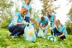 Collect volunteer help with garbage. Young people volunteer as garbage collectors at an environmental action royalty free stock images