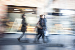 Young people walking in shopping centre, zoom effect, motion blur. People walking in shopping centre, zoom effect, motion blur royalty free stock photos