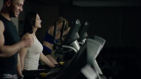 Young people walking on the treadmill smiling stock video