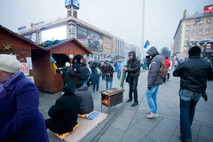 Young people warm themselves by the vintage stove on the street during the week of pro-European protest Stock Images